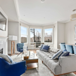 boston living room with light colored walls and blue accents over grey furniture