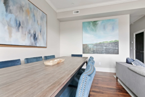 boston dining room with light colored walls and blue dining chairs with colorful art